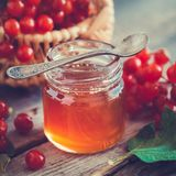 玫瑰色瓶子的蜂蜜和的Guelder或在木书桌上的荚莲属的植物莓果 库存照片
