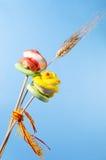 玫瑰色红色和黄色的糖和在蓝色背景的麦子耳朵 免版税库存照片
