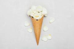 玫瑰色花冰淇凌在奶蛋烘饼锥体的在从上面浅灰色的背景,美丽的花卉装饰,葡萄酒颜色,平的位置 免版税库存图片