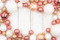 玫瑰色金子、白色和金装饰品圣诞节框架在白色木头 免版税库存图片