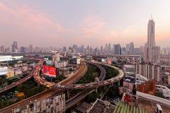 玫瑰色黄昏的曼谷与摩天大楼在背景和繁忙的交通中在高的高速公路&圆互换 免版税库存图片