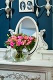 玫瑰花束在一个清楚,圆,玻璃花瓶的在与镜子的桌上 免版税库存照片