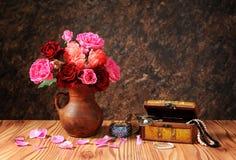 玫瑰花束在的陶瓷花瓶和首饰 免版税库存图片