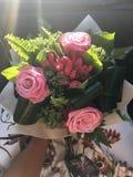 玫瑰花束在阳光下的与一件开花的礼服 库存照片