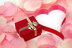玫瑰花瓣、心脏和华伦泰当前箱子背景 免版税库存图片