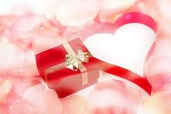 玫瑰花瓣、心脏和华伦泰当前箱子背景 库存图片