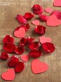 玫瑰花瓣和心形在木背景 库存图片