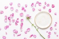 玫瑰花瓣和板材平的位置在妇女桌面景色大模型 免版税库存照片