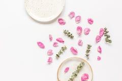 玫瑰花瓣和板材平的位置在妇女桌面景色大模型 免版税库存图片