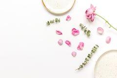 玫瑰花瓣和板材平的位置在妇女桌面景色大模型 图库摄影