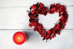 玫瑰花瓣和红色蜡烛的心脏 免版税库存照片