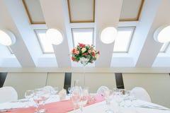 玫瑰迷人的花束在一张桌上的在豪华现代餐馆 免版税库存照片