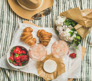 玫瑰酒红色,草莓,新月形面包,咸味干乳酪乳酪,花平位置  免版税图库摄影