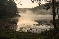 环境友好室外活动,野营在平静的湖河岸的早晨用阳光和薄雾水 免版税图库摄影
