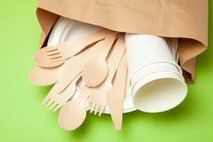 环境友好的一次性器物由竹木头和纸制成在绿色背景 被装饰的匙子,叉子,刀子 库存照片