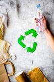 环境友好的生活 回收在废纸,塑料,在灰色背景顶视图的聚乙烯中的绿皮书标志 免版税库存图片