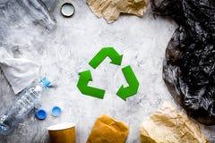 环境友好的生活 回收在废纸,塑料,在灰色背景顶视图的聚乙烯中的绿皮书标志 免版税库存照片