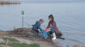 环境挽救,孩子男孩帮助从塑料垃圾的母亲志愿活动家干净的被污染的河堤防和 影视素材
