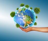 环境的生态概念与树的耕种的在地面上的在手上 背景地球充分的行星星形 实际 免版税库存照片