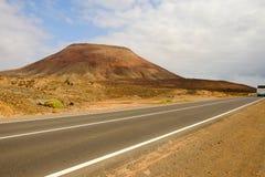 环境美化与一座山和一条路有一辆公共汽车的在费埃特文图拉岛 库存图片