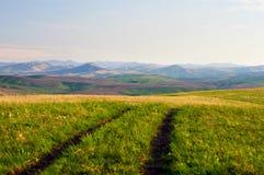 环境美化与乡下公路在春天阿尔泰山山麓小丘  库存照片