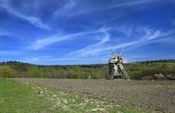 环境美化与在一个被犁的领域的一台风车 免版税库存照片
