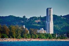 环境美化与在城市的背景的一个拥挤城市海滩有摩天大楼的 假日在热带 免版税库存照片