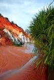 环境美化与在红色岩石和密林之间的河。越南 免版税库存图片