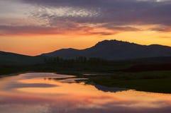 环境美化与在阿尔泰山山麓小丘的日落五颜六色的湖反射  免版税库存图片