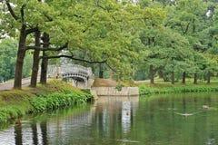 环境美化与在水的老桥梁在宫殿公园 免版税库存图片