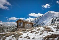 环境美化与多雪的客舱小屋和蓝天 免版税库存照片