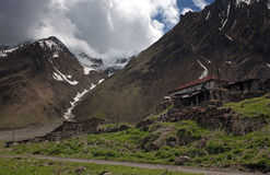 环境美化与多雪的山、冰川和云彩背景的一个老被放弃的房子  免版税库存照片