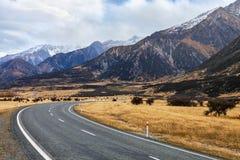 环境美化与山弯曲道路在库克山国家公园在多云秋天天,南岛,新西兰 免版税库存图片