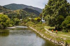环境美化与橙色衣裳的三个消遣骑自行车者沿着河在纳尔逊,新西兰 图库摄影