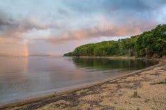 环境美化与沙滩、剧烈的天空、多雨云彩和彩虹 免版税图库摄影