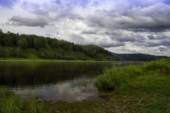 环境美化与河、山和森林岸的 与暴风云的天空在河 库存照片
