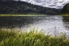 环境美化与河、山和森林岸的 与暴风云的天空在河 免版税库存图片
