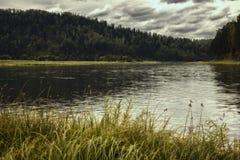环境美化与河、山和森林岸的 与暴风云的天空在河 免版税库存照片