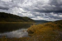 环境美化与河、山和森林岸的 与暴风云的天空在河 免版税图库摄影