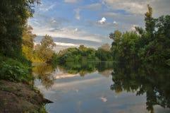 环境美化与河、森林、云彩和反射 免版税图库摄影