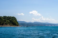 环境美化与海、山和一条小的小船 库存照片