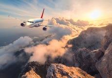环境美化与白色乘客飞机、山、海和橙色天空 库存照片