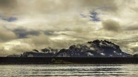 环境美化与背景山树和薄雾和一个湖前面的,在重的雨天以后 恶劣的采光条件 库存图片