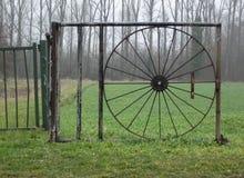 环境美化与通过铁轮子和草甸被看见的树 免版税库存照片