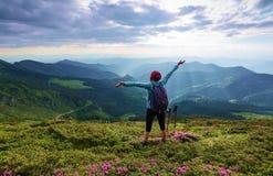 环境美化与高山,太阳光芒通过云彩来临 有后面大袋的女孩在草坪停留 免版税库存图片