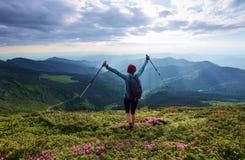 环境美化与高山,太阳光芒通过云彩来临 有后面大袋的女孩在草坪停留 免版税库存照片