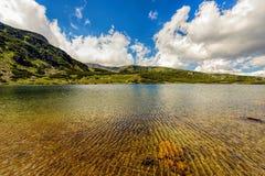 环境美化与Fagaras高地的一个冰河湖  免版税库存图片