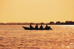 环境美化在一条小船的日落有钓鱼在潘塔纳尔湿地的渔夫的 免版税库存图片