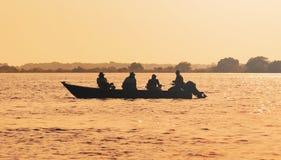 环境美化在一条小船的日落有钓鱼在潘塔纳尔湿地的渔夫的 图库摄影