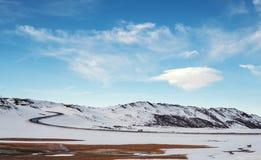 环境美化在与乡下公路和双突透镜的云彩的冬天在蓝天 库存图片